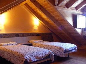 Dormitorio con dos camas en el bajo-cubierta